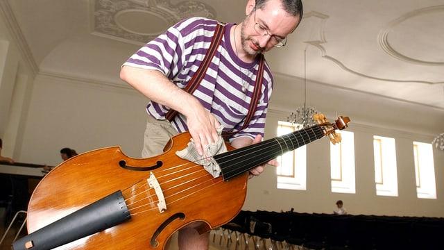 Ein Gambenspieler putzt sein Instrument.