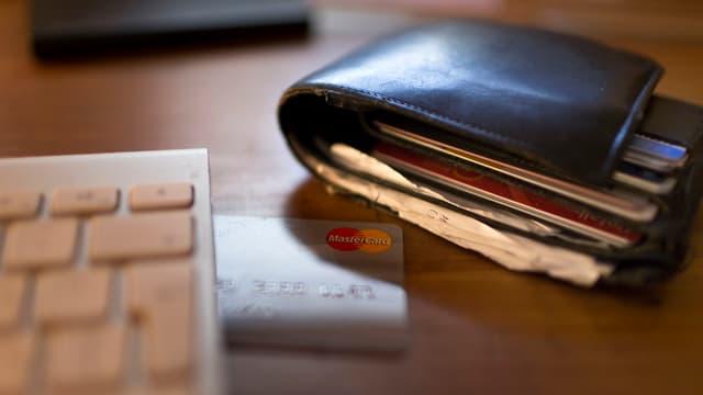 Purtret d'ina bursa e cartas da credit avant la tastatura da computer.