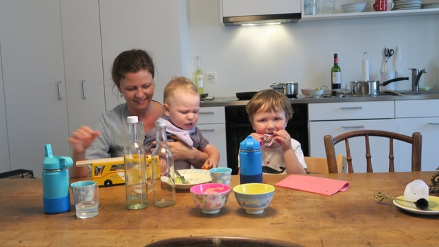 Eine junge Mutter mit zwei Kindern an einem Küchentisch beim Essen.