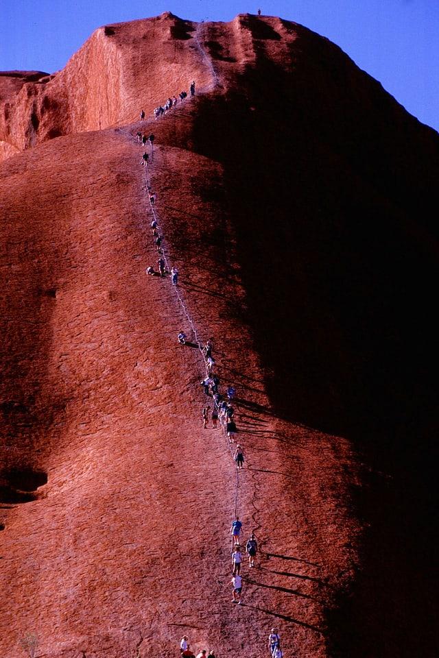 Touristen steigen auf den Heiligen Berg der Aborigines