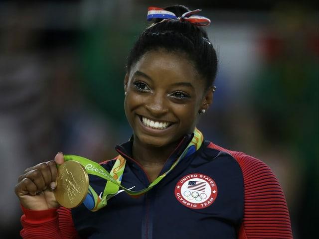 Simone Biles strahlt mit der Goldmedaille um den Hals in die Kamera.
