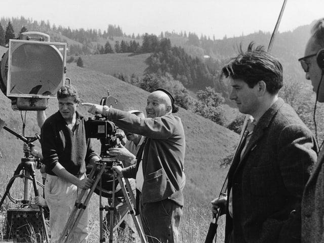 Franz Schnyder zeigt neben der Kamera stehend mit energischem Blick auf das Set. Der Kameraassistent sowie ein Filmscheinwerfer stehen neben der Kamera. Im Vordergrund der Tonmeister.