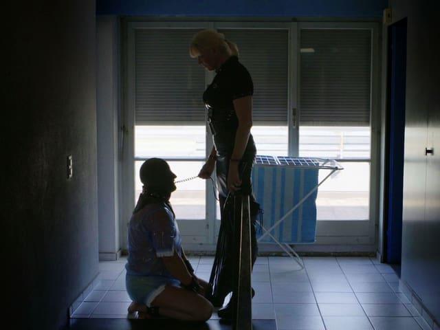 Ein maskierter Mann apportiert wie ein Hund vor seiner Herrin.