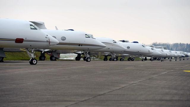Business-Jets aufgereiht am Pistenrand.