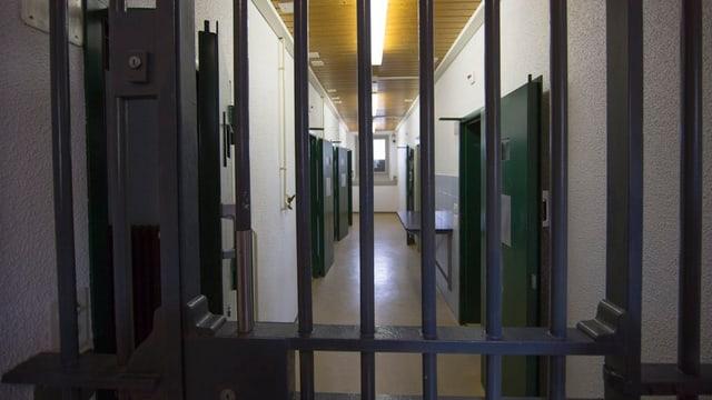 Gefängnisstäbe durch die man einen Gang sieht.