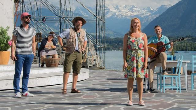 Eine Frau singt auf einer Bühne. Auch einige Herren stehen da.