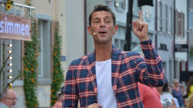 Roman Kilchsperger zeigt mit dem Zeigefinger nach oben und lächelt verschmitzt.