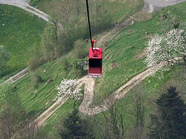 Eine rote Seilbahn schwebt über der Landschaft