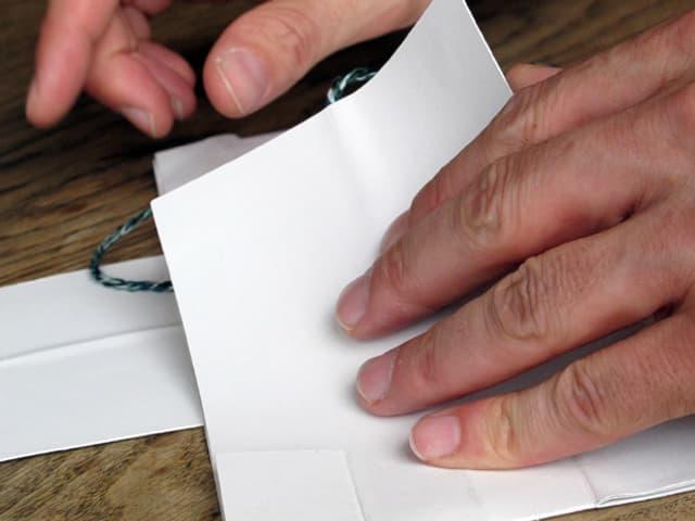 Hände auf einem weissen Papier.