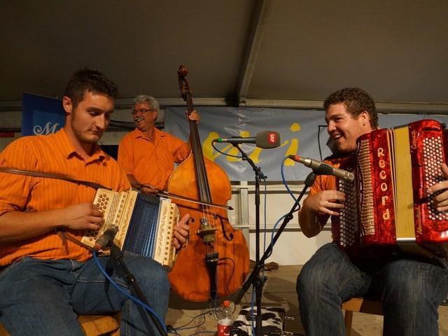 Drei Volksmusikanten in orangen Hemden mit Schwyzerörgeli, Kontrabass und Akkordeon.