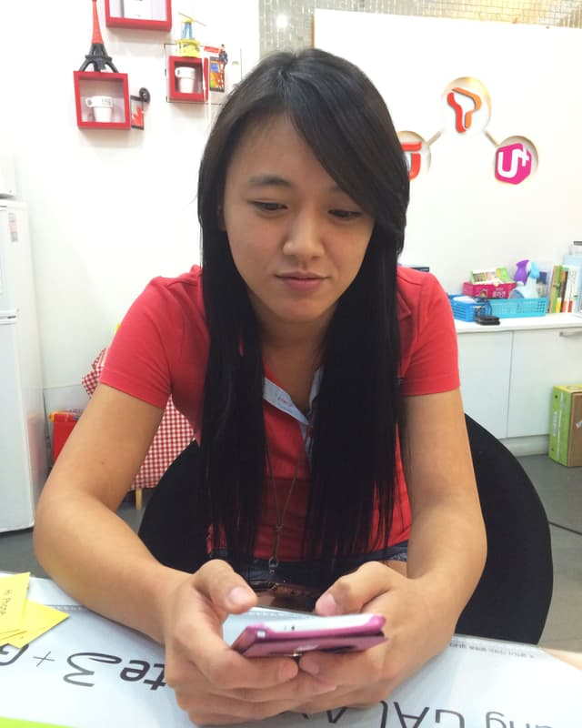 Eine koreanische junge Frau schaut auf ein rosafarbenes Smartphone.