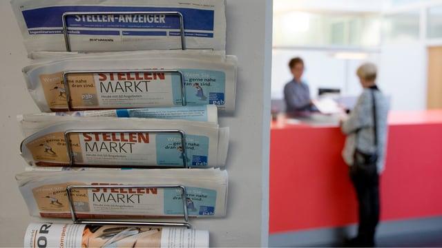Ein Zeitungshalter mit Stellenanzeigern, im Vordergrund links, zu sehen während dem eine Mitarbeiterin des Regionalen Arbeitsvermittlungszentrums RAV, links, am Schalter eine Frau berät.