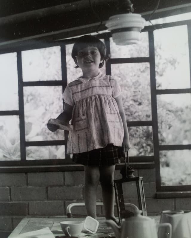 Ein kleines barfüssiges Mädchen steht mit einer Laterne und einem Zettel in der Hand auf einem Tisch.