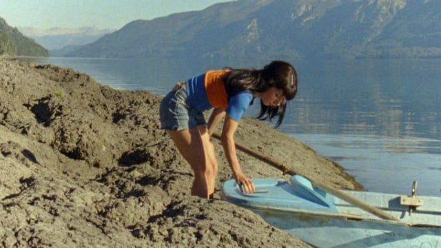 Eine junge Frau steht an einem steinigen Ufer neben einem Boot
