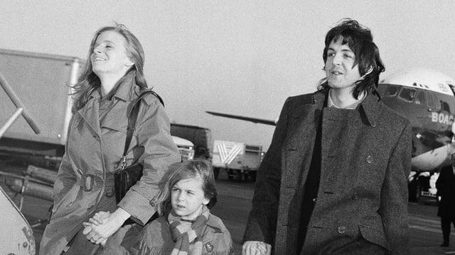 Paul McCartney mit Frau und Kind auf dem Rollfeld eines Flugplatzes.
