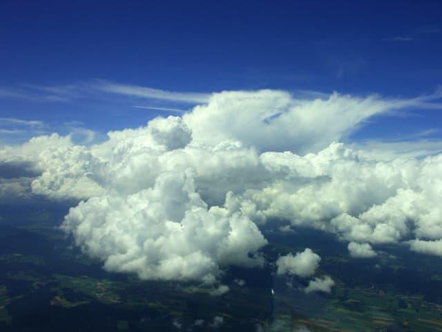 Flugaufnahme: blauer Himmel, unten grüne Landschaft, in der Mitte eine gigantische Wolke.