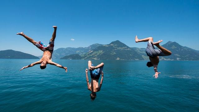Drei Knaben springen ins Wasser.