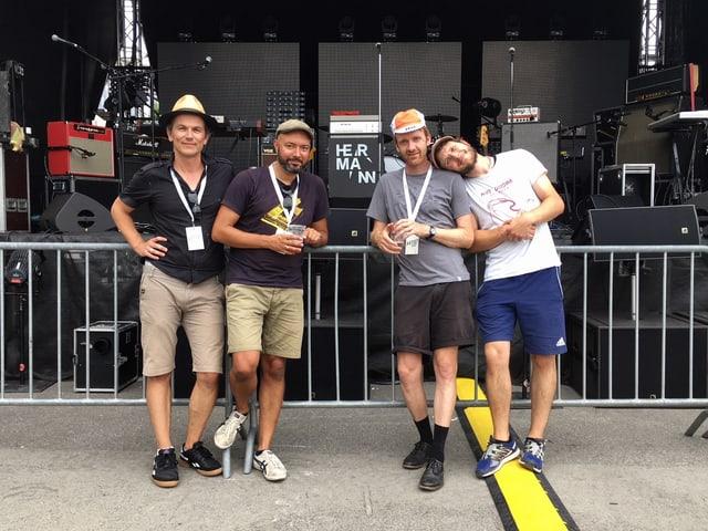 Vier Männer stehen vor einer Konzertbühne.