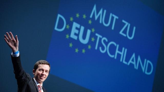 Lucke winkt vor einem blauen Hintergrund, dort steht «Mut zu Deutschland».