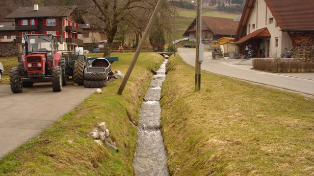 Der kleine Sandbach in der Gemeinde Kerns, ein Traktor fährt vorbei.