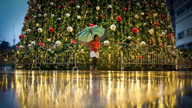 Ein kleines Mädchen trotzt dem Regen vor einem grossen Weihnachtsbaum in Kuala Lumpur.