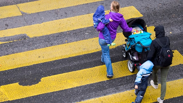 Eine Familie mit Kinderwagen überquert einen Fussgängerstreifen.
