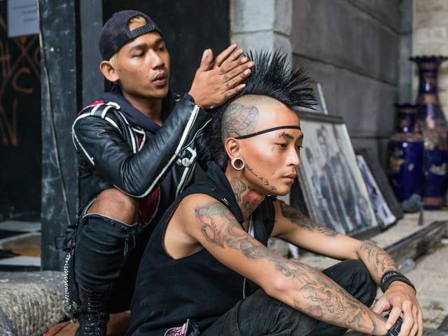 Ein Punk frisiert seinem Kollegen einen Irokesen.