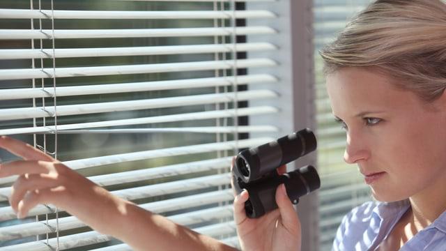 Eine Frau mit Videokamera beobachtet jemanden oder etwas durch eine Jalousie.