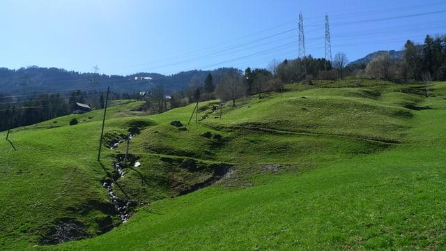 Blick auf das Rutschgebiet - im Hintergrund stehen zwei Masten von Hochspannungsleitungen