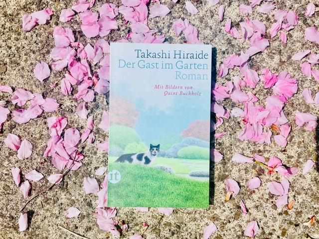 Der Roman «Saturo und das Geheimnis des Glücks» von Hiro Arikawa liegt auf Kirschblüten