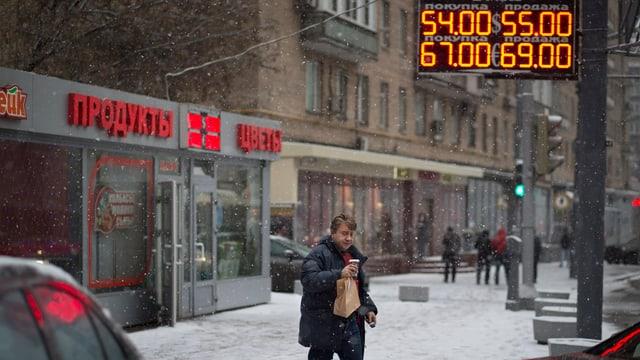 Mann überquert die Strasse, im Hintergrund digitale Anzeige von Währungskursen.