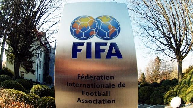 Ina platta fier cun inscrit «FIFA». Sur il logo stattan duas ballas da ballape che vesan era ora sco dus bglobs terresters.