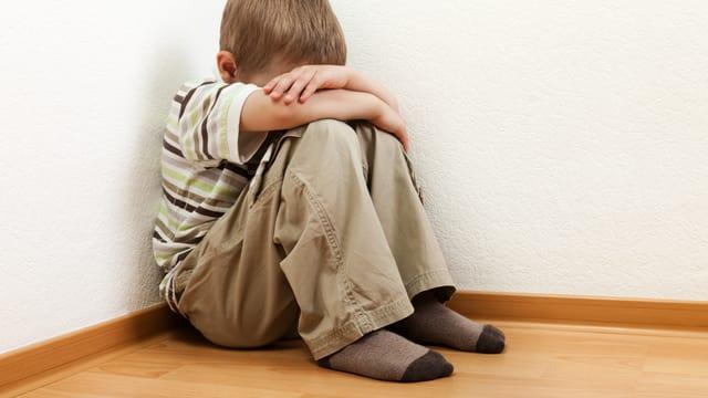 Ein Kind sitzt in einer Ecke, den Kopf zwischen den Armen vergraben.