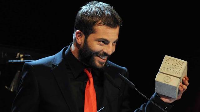 Zu sehen ist der Musiker Bligg. Er trägt schwarzen Anzug, schwarzes Hemd, schwarzen Bart und er lächelt. In der linken Hand hält er den Betonklotz, der den Swiss Music Award darstellt.