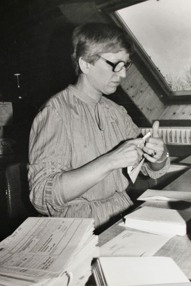 Schwarzweiss Bild: Frau mit Kleid, kurzen Haaren und grosser Brille sitzt an einem Schreibtisch und tütet gerade einen Brief in ein Couvert ein.