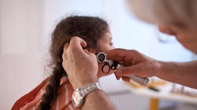 Ärztin untersucht das Ohr eines Kindes