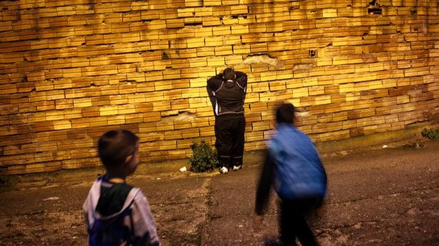 Drei spielende Kinder vor einer glänzenden Wand.