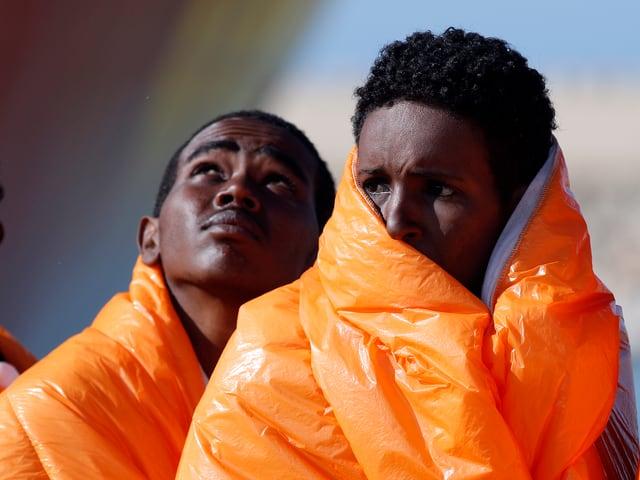 Zwei schwarze Jugendliche sind eingehüllt in orange Wärmedecken. Sie schauen besorgt; einer in den Himmel, der andere nach links.