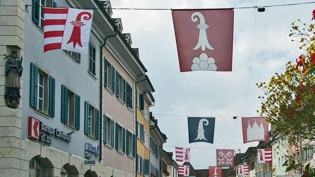 Strasse mit Kantons- und Gemeindeflaggen im Kanton Jura.