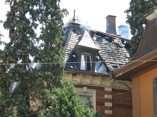 Blick auf den Dachgiebel mit einem Dachfenster. Man sieht Rauch aus dem Fenster aufsteigen.