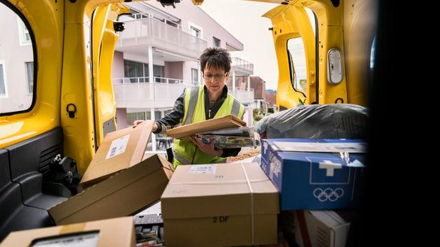 Ina postina che piglia pachets ord in auto da la posta.