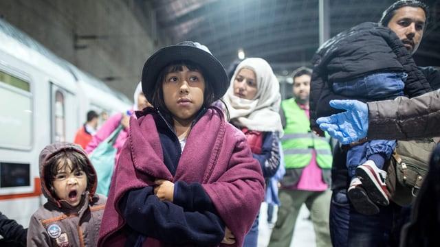 Flüchtlingsfamilie auf einem Bahnhof in Deutschland, links im Bild ein Zug