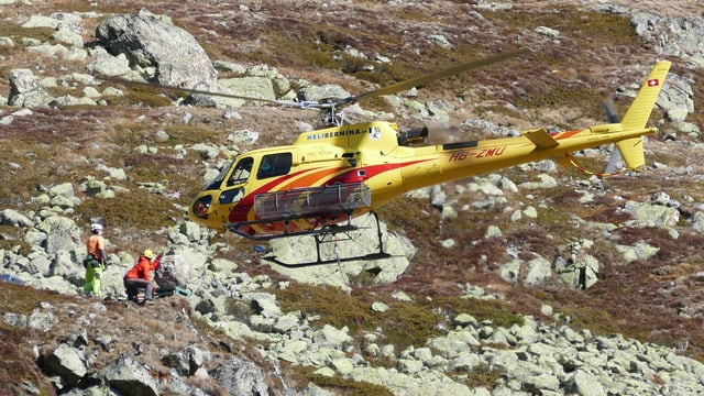 Ein gelber Helikopter hat einen künstlichen Stein mit Drahseil zur Startrampe geflogen.