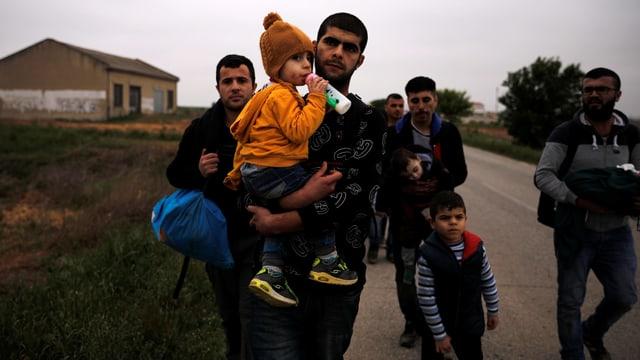 Männer mit Kinder, die den Fluss Evros überquert haben