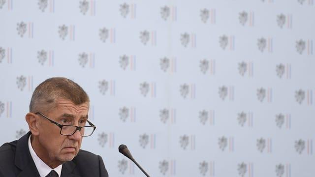 Babis mit Brille vor einem Mikrofon.
