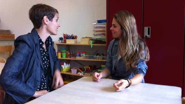 Esseiva und die Lehrerin sitzen an einem kleinen Tisch und reden.