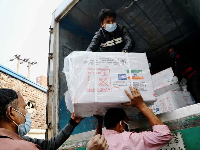 Arbeiter entladen in Dhaka einen Kleintransporter mit COVID-19-Impfstoffen