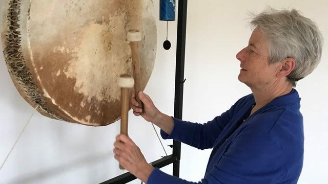 Musiktherapeutin Sandra Lutz spielt auf einer grossen aufgehängten Trommel.