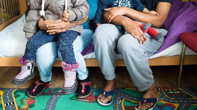 Flüchtlingseltern mit Kindern auf dem Schoss sitzen auf einem Bett in einer Asyslunterkunft.