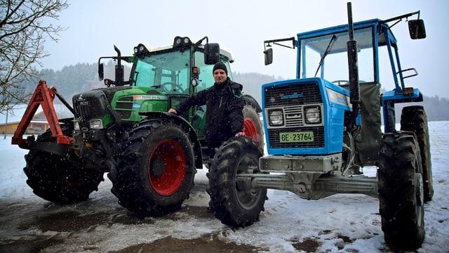 SRF-Digitalredaktor posiert zwischen zwei Traktoren.